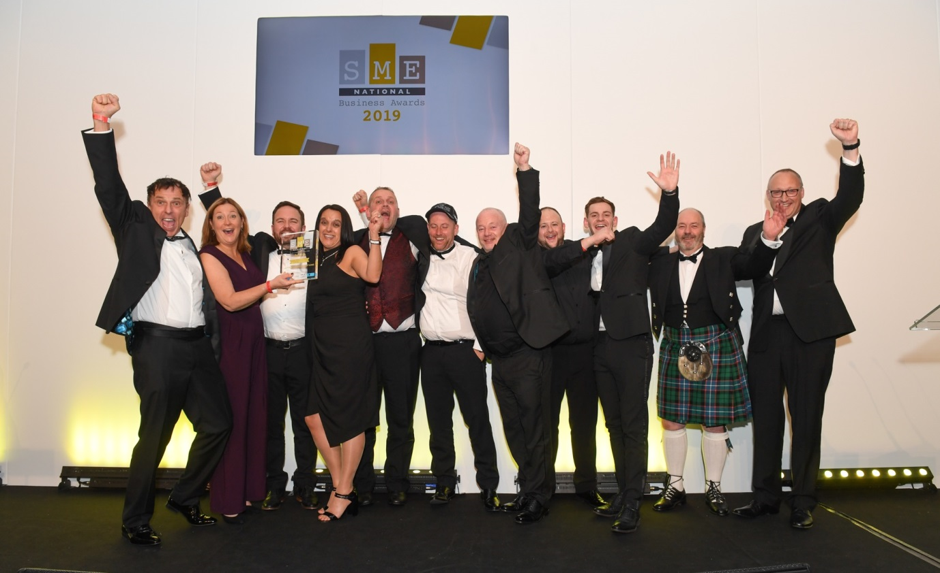 AGS team celebrating at the SME awards, holding one person holds award, 10 other people have their hands in the air.
